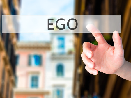 pretentious: Ego - Hand pressing a button on blurred background concept . Business, technology, internet concept. Stock Photo