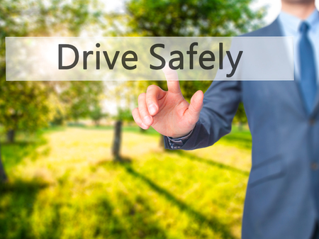 safely: Drive Safely - Businessman hand pressing button on touch screen interface. Business, technology, internet concept. Stock Photo