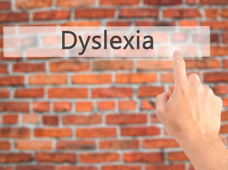 dyslexia: Dyslexia - Hand pressing a button on blurred background concept . Business, technology, internet concept. Stock Photo