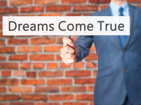 dreamscape: Dreams Come True - Businessman hand holding sign. Business, technology, internet concept. Stock Photo Stock Photo