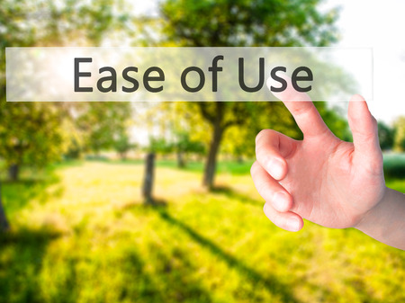 with ease: Ease of Use - Hand pressing a button on blurred background concept . Business, technology, internet concept. Stock Photo Stock Photo