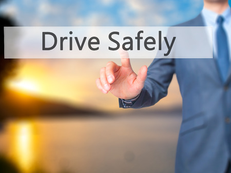 drive safely: Drive Safely - Businessman hand pressing button on touch screen interface. Business, technology, internet concept. Stock Photo