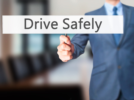 drive safely: Drive Safely - Businessman hand holding sign. Business, technology, internet concept. Stock Photo