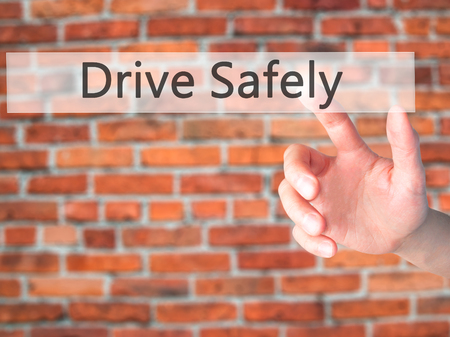 safely: Drive Safely - Hand pressing a button on blurred background concept . Business, technology, internet concept. Stock Photo