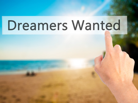 innovator: Dreamers Wanted - Hand pressing a button on blurred background concept . Business, technology, internet concept. Stock Photo