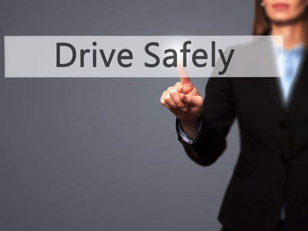 drive safely: Drive Safely - Businesswoman hand pressing button on touch screen interface. Business, technology, internet concept. Stock Photo