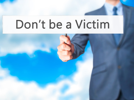 sufferer: Dont be a Victim - Businessman hand holding sign. Business, technology, internet concept. Stock Photo