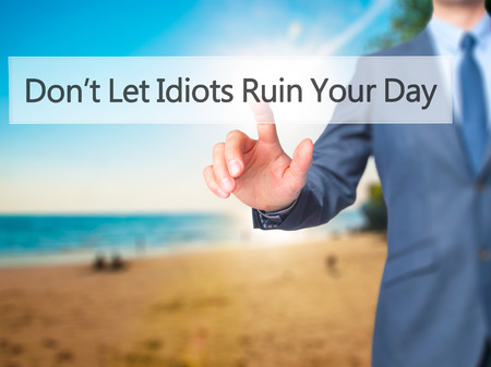 stupidity: Dont Let Idiots Ruin Your Day - Businessman hand pressing button on touch screen interface. Business, technology, internet concept. Stock Photo Stock Photo