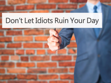 stupidity: Dont Let Idiots Ruin Your Day - Businessman hand holding sign. Business, technology, internet concept. Stock Photo