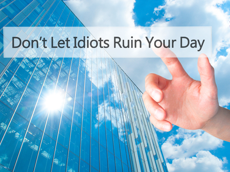 irrelevant: Dont Let Idiots Ruin Your Day - Hand pressing a button on blurred background concept . Business, technology, internet concept. Stock Photo