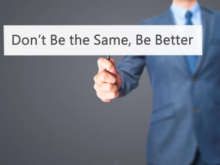 better: Dont Be the Same, Be Better - Businessman hand holding sign. Business, technology, internet concept. Stock Photo