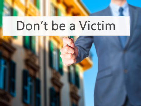 intimidated: Dont be a Victim - Businessman hand holding sign. Business, technology, internet concept. Stock Photo