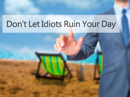 unprofessional: Dont Let Idiots Ruin Your Day - Businessman hand pressing button on touch screen interface. Business, technology, internet concept. Stock Photo Stock Photo