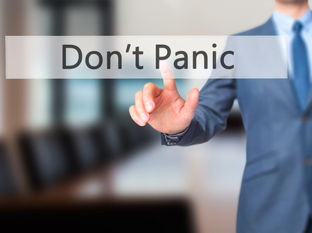 stay alert: Dont Panic - Businessman hand pressing button on touch screen interface. Business, technology, internet concept. Stock Photo