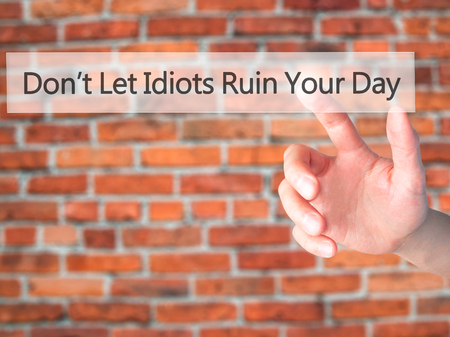naivety: Dont Let Idiots Ruin Your Day - Hand pressing a button on blurred background concept . Business, technology, internet concept. Stock Photo