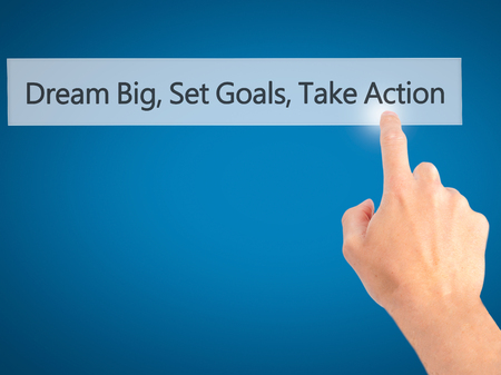 team leadership: Dream Big Set Goals Take Action - Hand pressing a button on blurred background concept . Business, technology, internet concept. Stock Photo