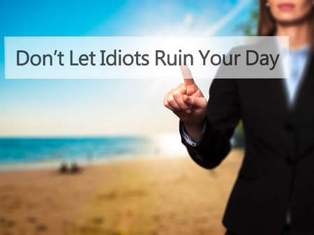 naivety: Dont Let Idiots Ruin Your Day - Businesswoman hand pressing button on touch screen interface. Business, technology, internet concept. Stock Photo