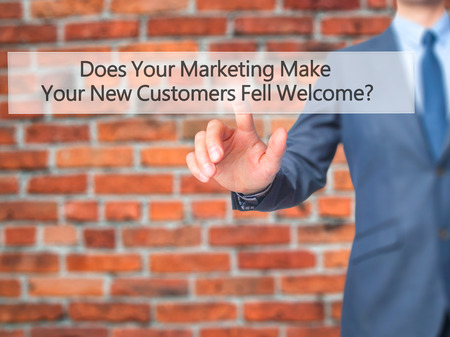 does: Does Your Marketing Make Your New Customers Fell Welcome - Businessman press on digital screen. Business,  internet concept. Stock Photo