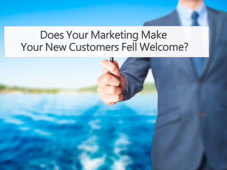 does: Does Your Marketing Make Your New Customers Fell Welcome - Business man showing sign. Business, technology, internet concept. Stock Photo