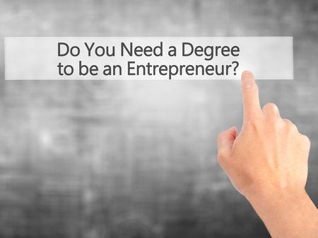 business degree: Do You Need a Degree to be an Entrepreneur ? - Hand pressing a button on blurred background concept . Business, technology, internet concept. Stock Photo