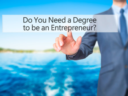 business degree: Do You Need a Degree to be an Entrepreneur ? - Businessman hand touch  button on virtual  screen interface. Business, technology concept. Stock Photo