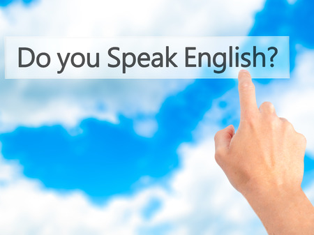 fluent: Do you Speak English ? - Hand pressing a button on blurred background concept . Business, technology, internet concept. Stock Photo