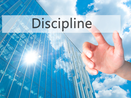 disciplined: Discipline - Hand pressing a button on blurred background concept . Business, technology, internet concept. Stock Photo