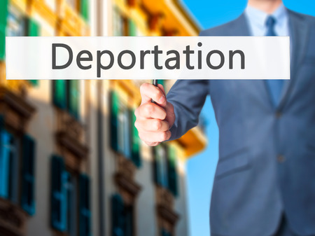 deportation: Deportation - Businessman hand holding sign. Business, technology, internet concept. Stock Photo
