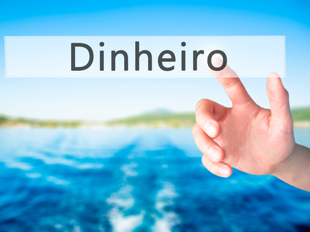 debt goals: Dinheiro (Money in Portuguese) - Hand pressing a button on blurred background concept . Business, technology, internet concept. Stock Photo Stock Photo