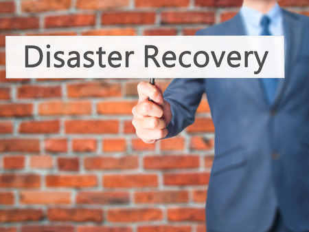 Disaster Recovery - Businessman hand holding sign. Business, technology, internet concept. Stock Photo Imagens - 59294169
