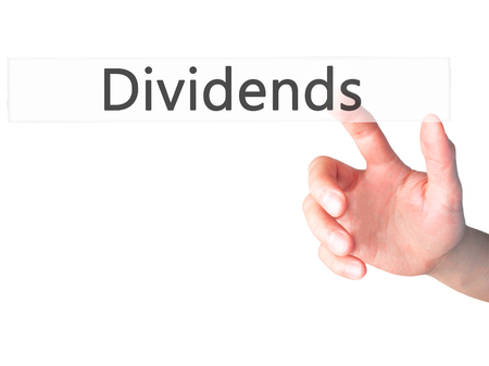 dividends: Dividends - Hand pressing a button on blurred background concept . Business, technology, internet concept. Stock Photo