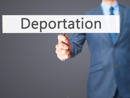 naturalization: Deportation - Businessman hand holding sign. Business, technology, internet concept. Stock Photo