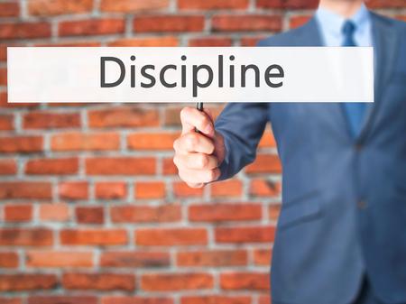 disciplined: Discipline - Businessman hand holding sign. Business, technology, internet concept. Stock Photo