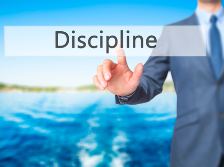 disciplined: Discipline - Businessman hand pushing button on touch screen. Business, technology, internet concept. Stock Image