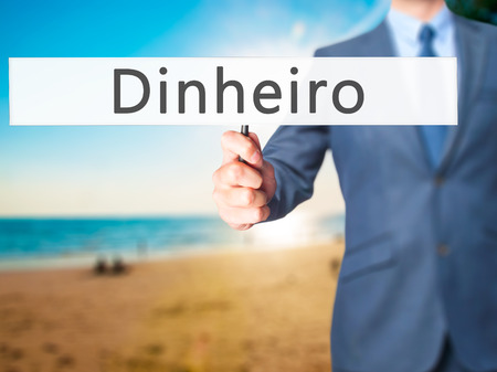 earn more: Dinheiro (Money in Portuguese) - Businessman hand holding sign. Business, technology, internet concept. Stock Photo Stock Photo