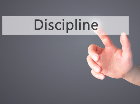 Discipline - Hand pressing a button on blurred background concept . Business, technology, internet concept. Stock Photo