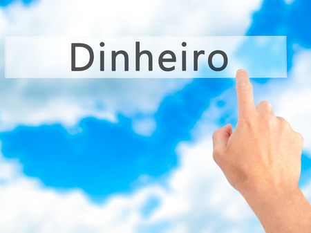 earn more: Dinheiro (Money in Portuguese) - Hand pressing a button on blurred background concept . Business, technology, internet concept. Stock Photo Stock Photo