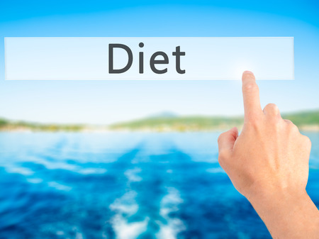 nutricion: Diet - Hand pressing a button on blurred background concept . Business, technology, internet concept. Stock Photo Stock Photo