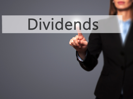 dividends: Dividends - Business woman point finger on push touch screen and pressing digital virtual button. Business, technology, internet concept. Stock Photo