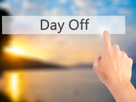 off day: Day Off - Hand pressing a button on blurred background concept . Business, technology, internet concept. Stock Photo