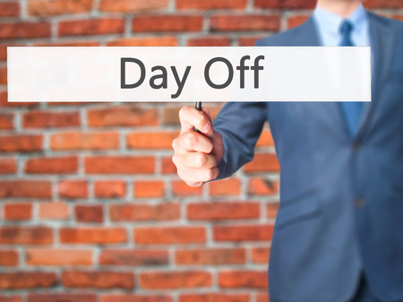 off day: Day Off - Businessman hand holding sign. Business, technology, internet concept. Stock Photo