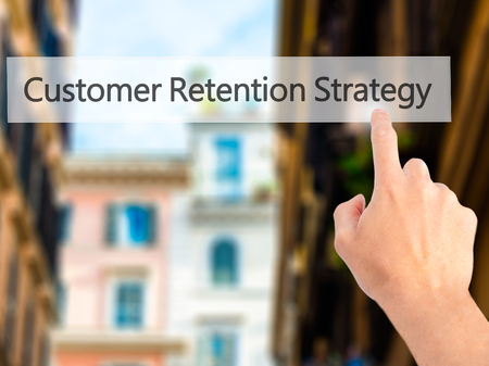 retention: Customer Retention Strategy - Hand pressing a button on blurred background concept . Business, technology, internet concept. Stock Photo