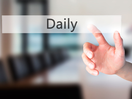 finished good: Daily - Hand pressing a button on blurred background concept . Business, technology, internet concept. Stock Photo