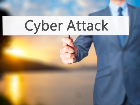 cyber attacks: Cyber Attack - Businessman hand holding sign. Business, technology, internet concept. Stock Photo Stock Photo