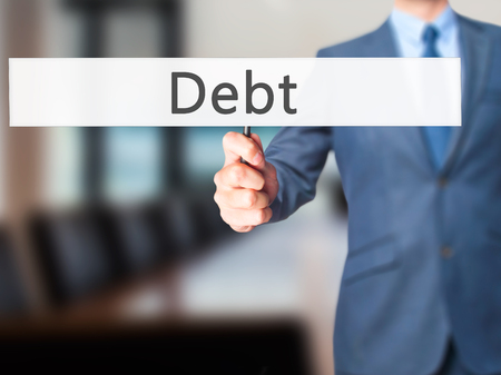 creditors: Debt - Businessman hand holding sign. Business, technology, internet concept. Stock Photo