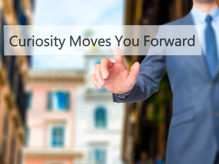 moves: Curiosity Moves You Forward - Businessman hand pushing button on touch screen. Business, technology, internet concept. Stock Image Stock Photo