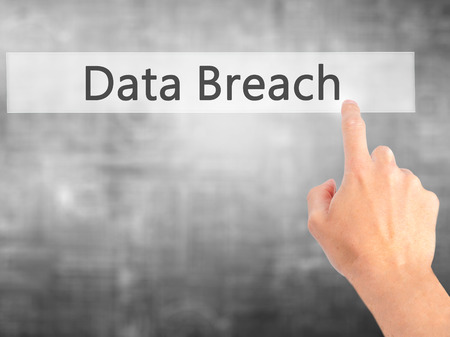 incursion: Data Breach - Hand pressing a button on blurred background concept . Business, technology, internet concept. Stock Photo