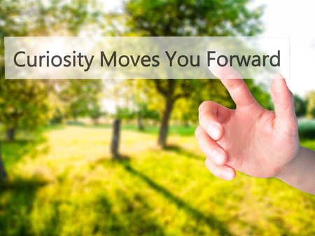 moves: Curiosity Moves You Forward - Hand pressing a button on blurred background concept . Business, technology, internet concept. Stock Photo