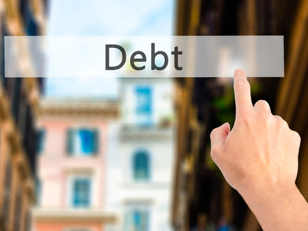 creditors: Debt - Hand pressing a button on blurred background concept . Business, technology, internet concept. Stock Photo