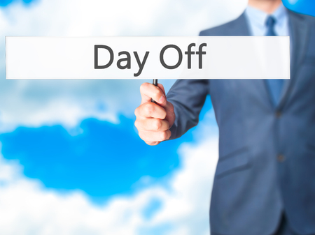 holidays vacancy: Day Off - Businessman hand holding sign. Business, technology, internet concept. Stock Photo